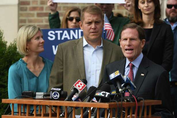U.S. Sen. Richard Blumenthal, D-Conn., speaks at the podium beside Darien man Scott Hapgood, left, and his wife, Kallie Hapgood, at Town Hall in Darien, Conn. Monday, Oct. 28, 2019 as the town shows support for Scott Hapgood in his manslaughter charge from a family vacation in Anguilla. Hapgood is facing a manslaughter charge regarding the death of a man who the family says attacked Hapgood in his hotel, forcing him to defend himself and his family. A revised autopsy report, based on new toxicology tests, determined the man died from a lethal dose of cocaine and not from injuries he sustained in the fight. U.S. Sen. Blumenthal, Darien First Selectman Jayme Stevenson, and friends and family are asking for a fair and transparent trial, as well as guaranteed safe passage, as Hapgood returns to Anguilla to face charges.