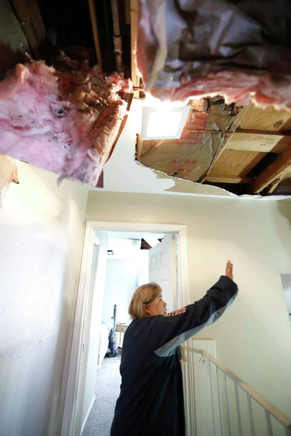 Maria Hernandez point to damage from her roof and ceiling as she and her family worked to move their belongings out as they sifted through their damaged home in the Bridgeland Lane area of Houston, Sunday, Jan. 26, 2020, after the Watson Grinding Manufacturing explosion early Friday morning.