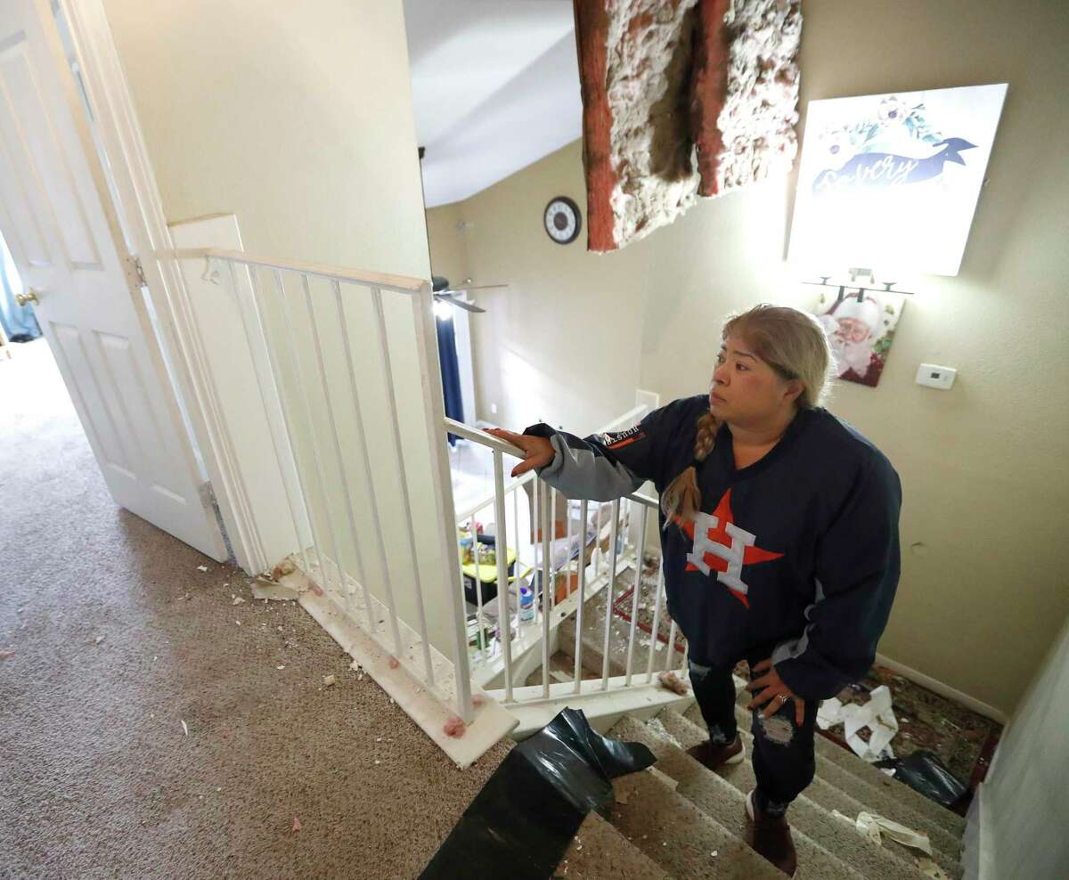 Maria Hernandez climbs her stairwell as she and her family worked to move their belongings out as they sifted through their damaged home in the Bridgeland Lane area of Houston, Sunday, Jan. 26, 2020, after the Watson Grinding Manufacturing explosion early Friday morning. Her ceiling collapsed even further after overnight rains.