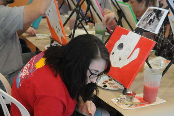 Sierra Murray of Elsah shows her dog, Moose, his portrait in progress Saturday during Paint Your Pet at The Vineyards at Grafton Winery. The event was led by Hope Retter of Custom Pawtraits of St. Louis.