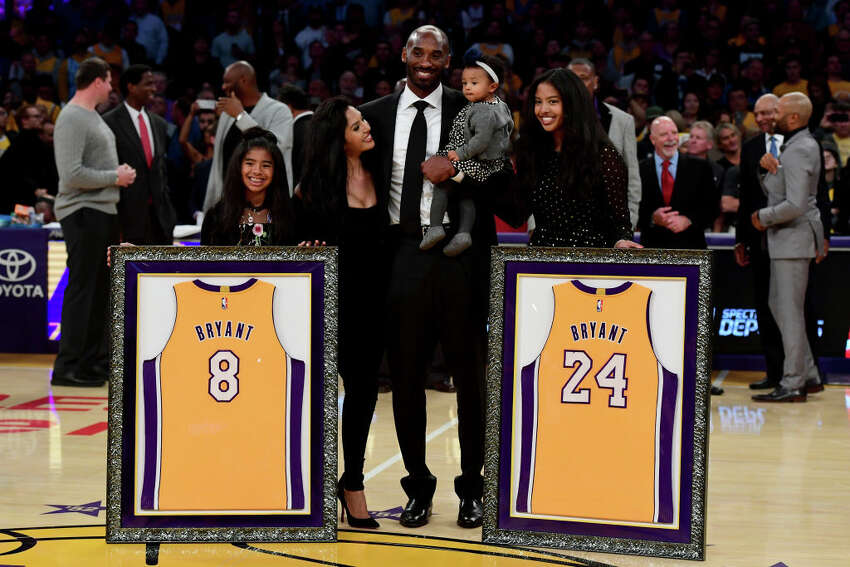 Kobe Bryant poses with his family at halftime after both his #8 and #24 Los Angeles Lakers jerseys are retired at Staples Center on December 18, 2017 in Los Angeles, California.