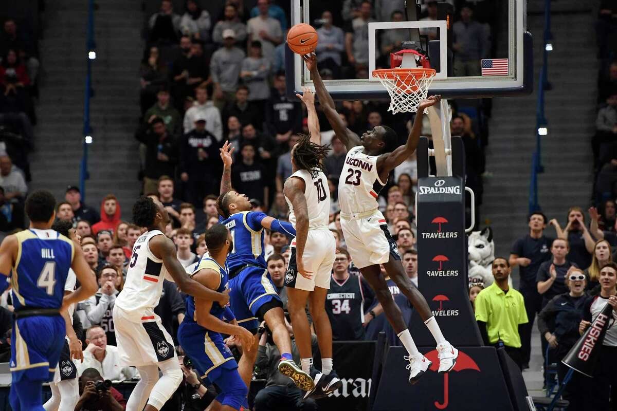 Connecticut's Akok Akok (23) blocks a shot-attempt by Tulsa's Darien Jackson (11) in the second half of an NCAA college basketball game, Sunday, Jan. 26, 2020, in Hartford, Conn. (AP Photo/Jessica Hill)