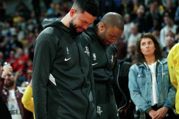 Houston Rockets guard Austin Rivers and forward P.J. Tucker react during a tribute to NBA star Kobe Bryant before an NBA basketball game against the Denver Nuggets, Sunday, Jan. 26, 2020, in Denver. Bryant died in a California helicopter crash Sunday. (AP Photo/David Zalubowski)