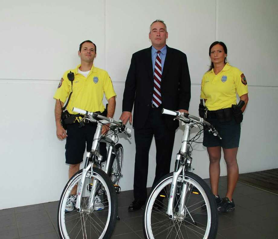 Westport Police Officer David Wolf, New Country Toyota General Manager James Tucker and  Detective Sereniti Dobson check out the two new bicycles recently donated to police by the auto dealership. Photo: Contributed Photo / Westport News