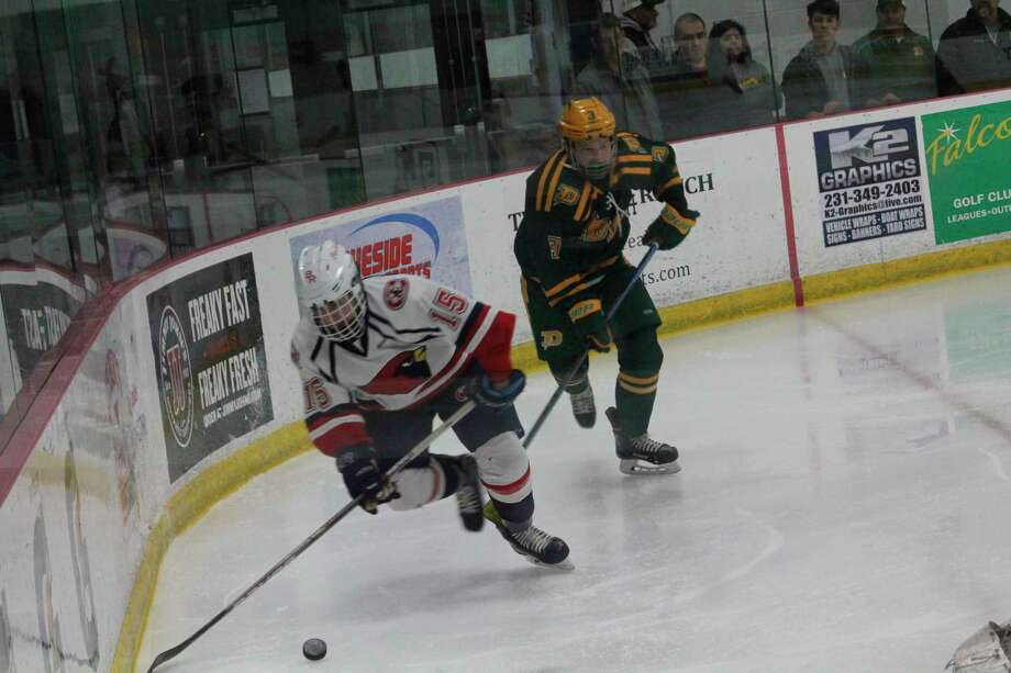 Big Rapids' Peter Ruttan (15) chases the puck against Midland Dow on Saturday. (Pioneer photo/John Raffel)