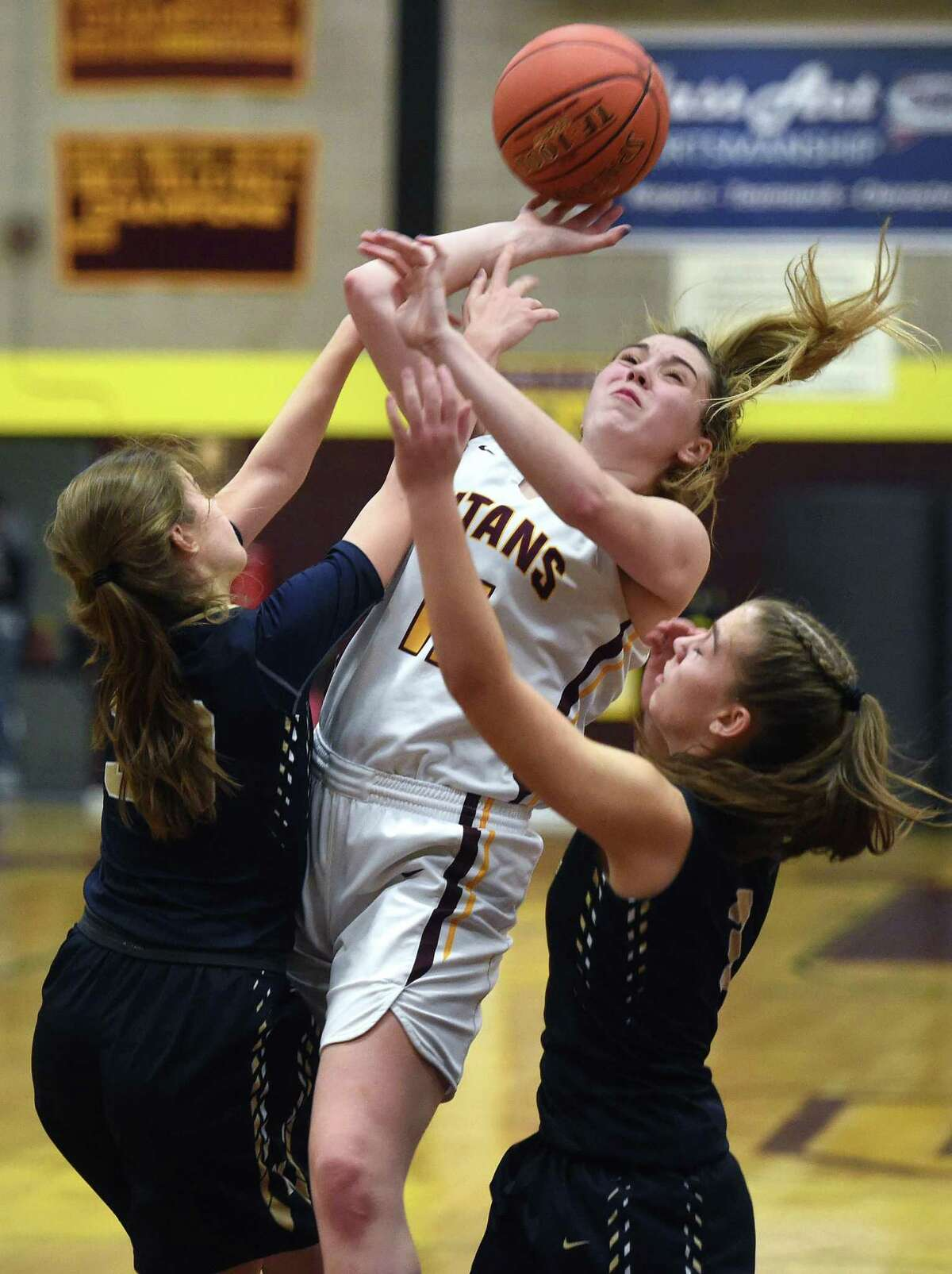 Maddi Larkin (center) of Sheehan is covered by Marliese Zocco (left) and Karissa Zocco of Newington as she goes to the basket in Wallingford on January 20, 2020.
