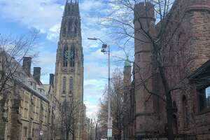 A view down High Street on the Yale University campus in New Haven, with Harkness Tower at left and Linsly-Chittenden Hall at right. Dwight Hall lies beyond Linsly-Chittenden; both are part of the Old Campus quad.