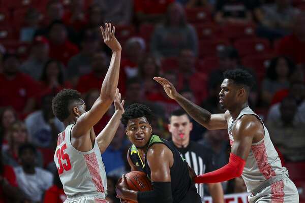 South Florida Bulls forward Michael Durr (4) is defended by Houston Cougars forward Fabian White Jr. (35) and center Chris Harris Jr. (1) during the first half of an NCAA game at the Fertitta Center Sunday, Jan. 26, 2020, in Houston.