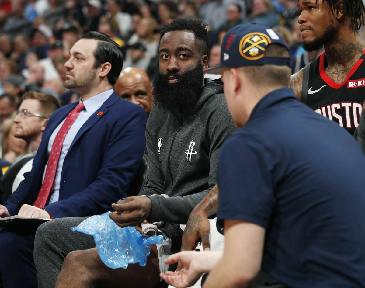 Houston Rockets guard James Harden, sidelined by a knee injury, unwraps his left leg while sitting on the bench in the first half of an NBA basketball game against the Denver Nuggets, Sunday, Jan. 26, 2020, in Denver. (AP Photo/David Zalubowski)