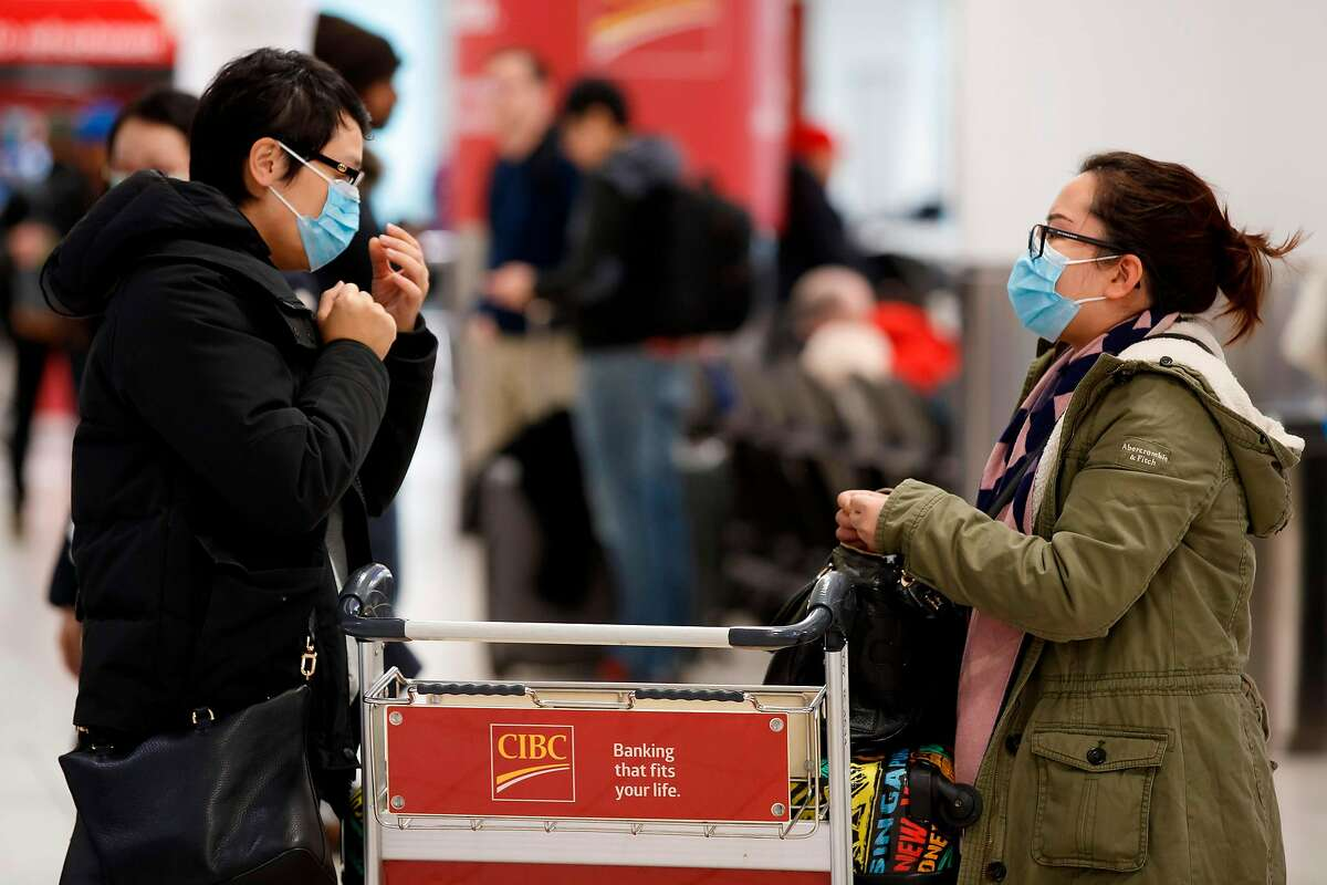 Travellers are seen wearing masks at the international arrivals area at the Toronto Pearson Airport in Toronto, Canada, January 26, 2020. - Toronto Public Health confirmed Saturday that a case of the novel coronavirus that originated in Wuhan, China is currently being treated in a Toronto Hospital. (Photo by Cole BURSTON / AFP) (Photo by COLE BURSTON/AFP via Getty Images)