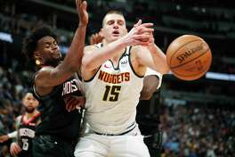 Denver Nuggets center Nikola Jokic, right, loses control of the ball as Houston Rockets forward Danuel House Jr. defends in the second half of an NBA basketball game Sunday, Jan. 26, 2020, in Denver.