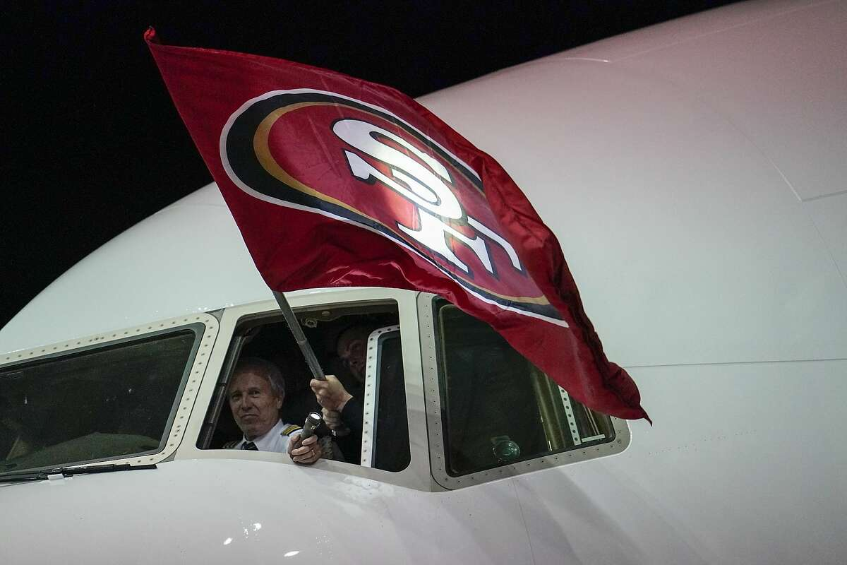 A pilot holds a flag as the San Francisco 49ers arrive for the NFL Super Bowl 54 football game Sunday, Jan. 26, 2020, at the Miami International Airport in Miami. (AP Photo/David J. Phillip)
