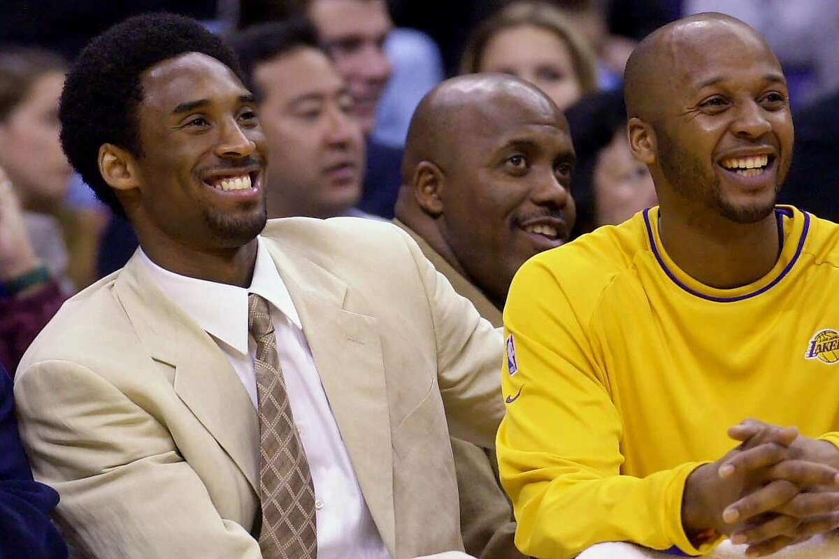Los Angeles Lakers' Tyronn Lue, left, Kobe Bryant, center, and Brian Shaw are all smiles as they watch their teammates play the Washington Wizards in the second quarter Friday, March 23, 2001, in Los Angeles. Bryant's sore left ankle already is feeling better, coach Phil Jackson said, but the star guard is expected to miss at least three games. Lakers guard Lue, who has a sprained ankle, was placed on the injured list Friday. (AP Photo/Kevork Djansezian)