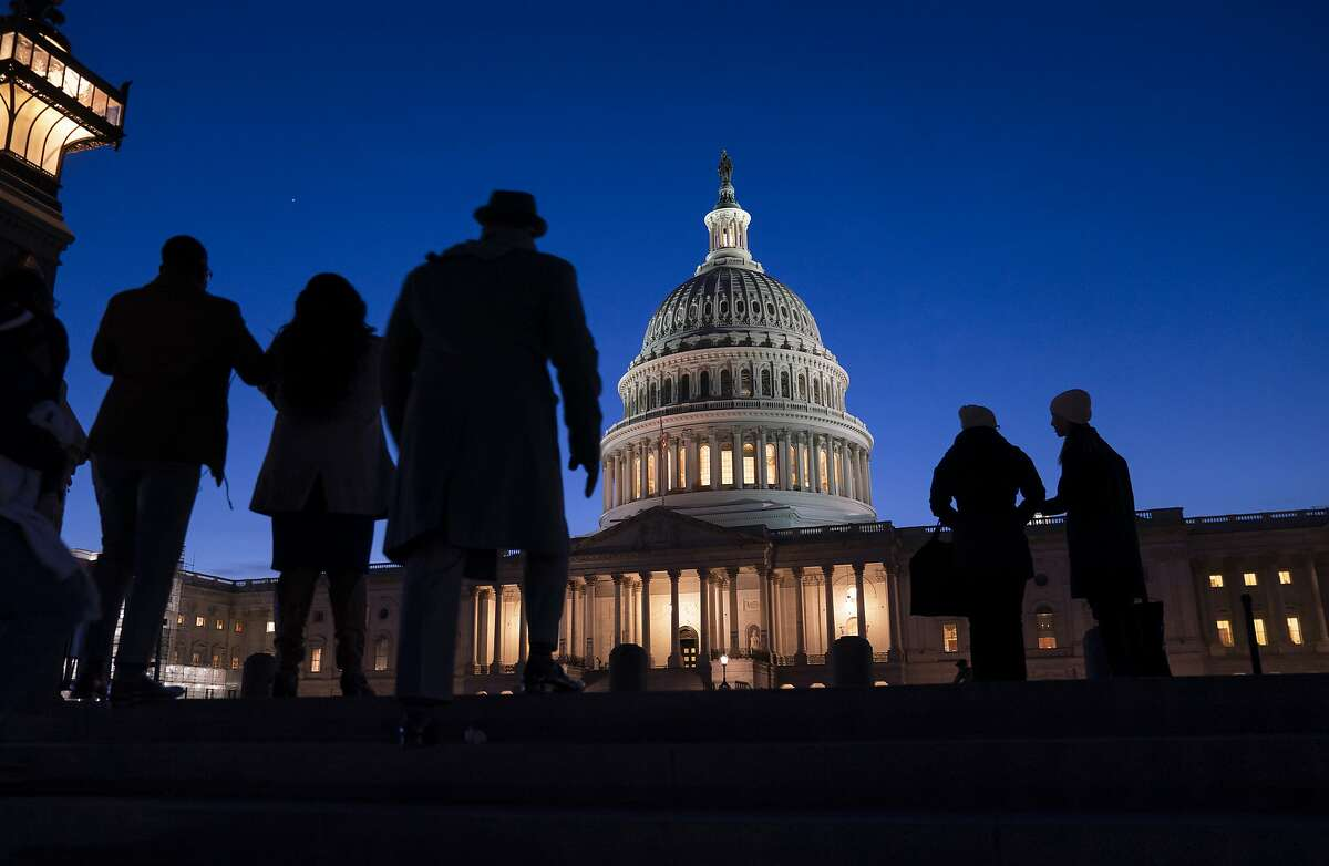 FILE - In this Jan. 22, 2020 file photo, night falls on the Capitol, in Washington during the impeachment trial of President Donald Trump. For all the gravity of a presidential impeachment trial, Americans don't seem to be giving it much weight. Web traffic and TV ratings tell a similar story, with public interest seeming to flag after the House voted last month to impeach a president for only the third time in U.S. history. (AP Photo/J. Scott Applewhite, File)