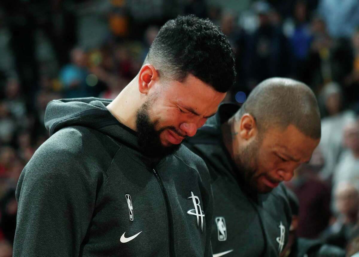Guard Austin Rivers, left, and forward P.J. Tucker fight tears during a tribute to Kobe Bryant before the Rockets' game at Denver on Sunday.