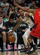 San Antonio Spurs' Dejounte Murray tries to see around the Toronto Raptors' defense as the Spurs host the Toronto Raptors at the AT&T Center in San Antonio, Texas, Jan. 26, 2020.