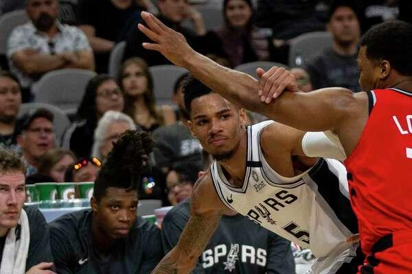 San Antonio Spurs' Dejounte Murray tries to see around the Toronto Raptors' defense as the Spurs host the Toronto Raptors at the AT&T Center in San Antonio, Texas, Jan. 26, 2020.