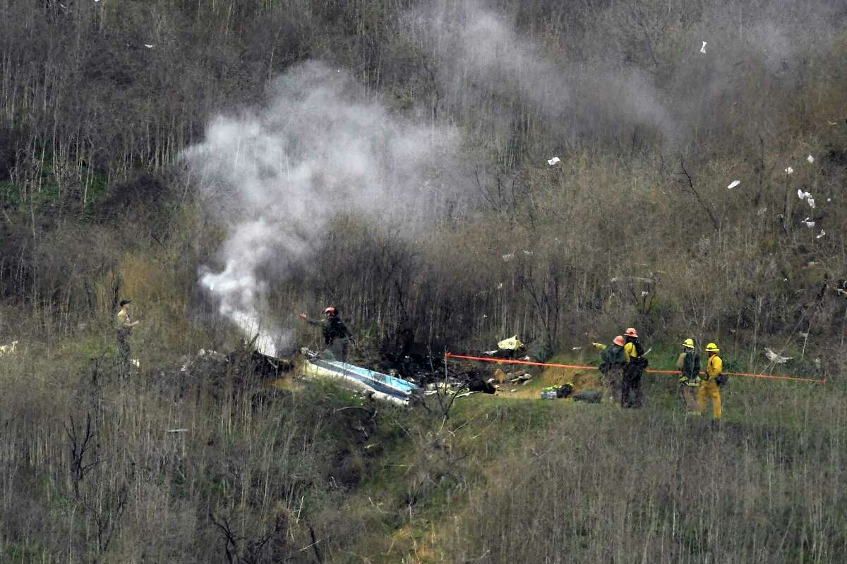 Firefighters work the scene of a helicopter crash Sunday, Jan. 26, 2020, in Calabasas, Calif. NBA basketball legend Kobe Bryant, his teenage daughter Gianna and three others were killed in the crash in Southern California on Sunday. (AP Photo/Mark J. Terrill)