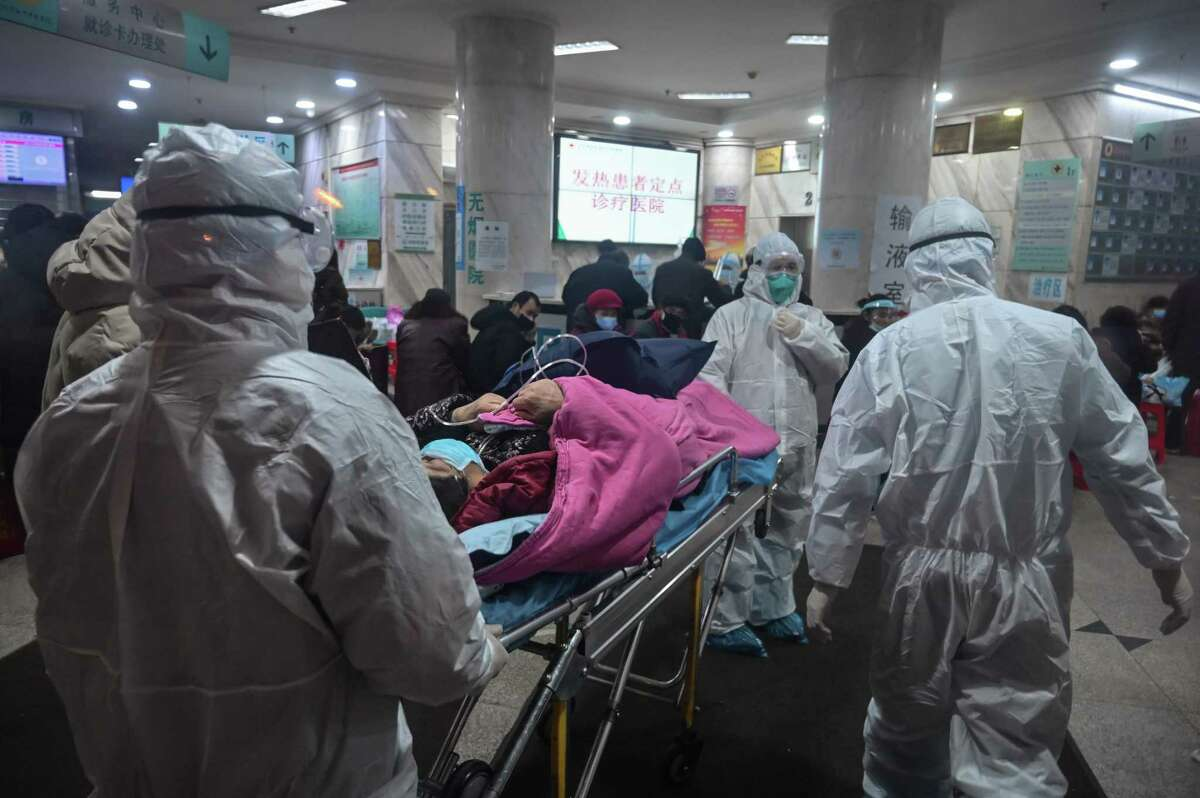 In this photo taken on January 25, 2020, medical staff wearing protective clothing to protect against a previously unknown coronavirus arrive with a patient at the Wuhan Red Cross Hospital in Wuhan. (Photo by Hector RETAMAL / AFP) (Photo by HECTOR RETAMAL/AFP via Getty Images)