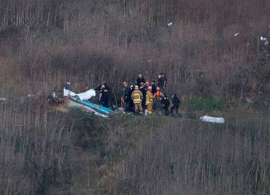 Los Angeles County Fire Department firefighters and coroner staff recover the bodies from the scene of a helicopter crash in Calabasas on January 26, 2020. Photo: Mark Ralston / AFP Via Getty Images