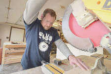 Shawn Lovekamp works on a creation for a client in his Jacksonville woodworking shop. The T-shirt was created for him by his daughter.