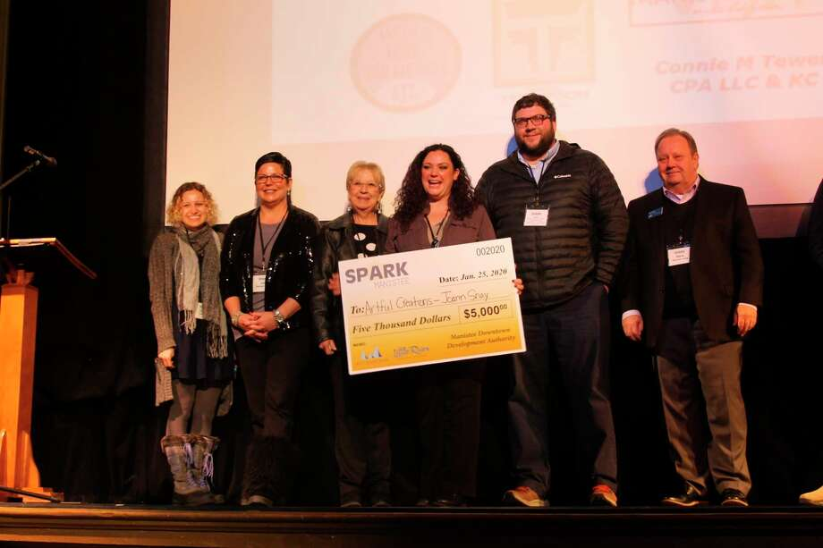 Judges and Manistee DDA executive director Caitlyn Berard (far left) stand with Spark Manistee winner Joann Snay (center) on Saturday at the Ramsdell Regional Center for the Arts. Snay, along with four other local entrepreneurs, gave a five-minute pitch for their business before the judges announced the winner. (Michelle Graves/News Advocate)