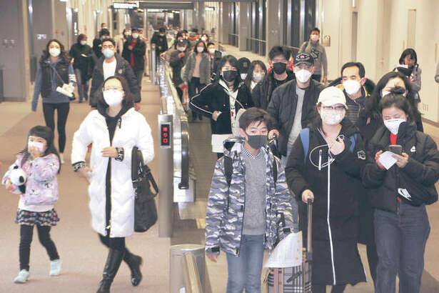 Passengers wearing face masks arrive at Narita airport in Narita, near Tokyo. Hong Kong has declared the outbreak of a new virus an emergency and have closed primary and secondary schools and blocked trains and flights from the city of Wuhan. Two cases of the virus have been confirmed in the U.S.