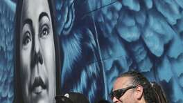 """Jacqueline Becerra, a local nursing director, pastor and philanthropist, poses with Los Otros art duo Shek Vega, left, and Nik Soupe as her portrait in a mural is unveiled on the side of Botello Food Store in the city's Westside, Sunday, Jan. 26, 2020. The with a mural is located in the underserved area of San Antonio where Becerra grew up. The mural – painted by local street art duo, Los Otros – is intended to inspire others in similar circumstances to reach their full potential. It was commissioned as part of Western Governors University's national """"Role Model Murals"""" project. On the left is her husband Pastor Henry Becerra."""