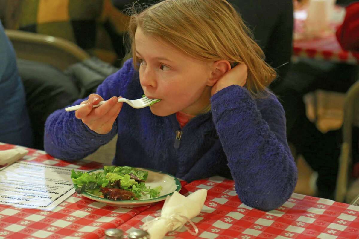 Allison Bond, 9, of Fairfield, digs into the salad at the 9th annual Deacons' Fund Pasta Dinner at First Church Congregational on Sunday, Jan. 26, 2020, in Fairfield, Conn.