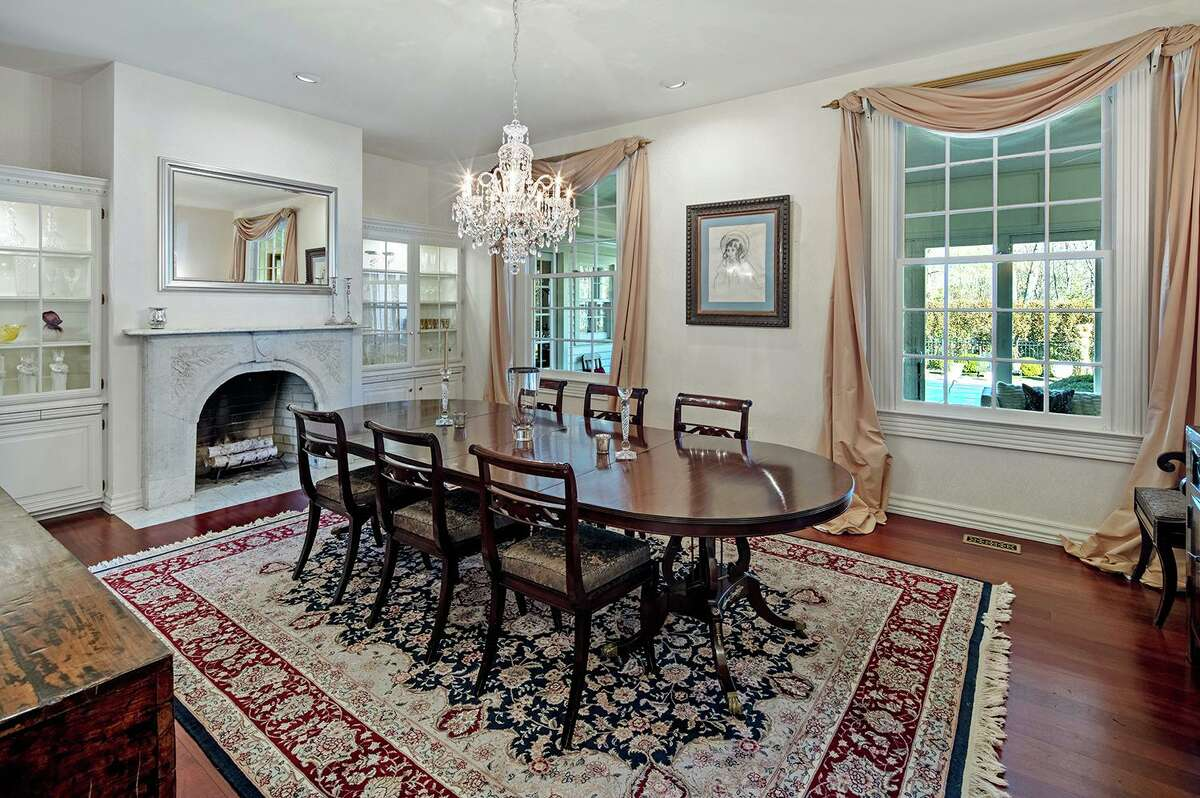 The banquet-sized formal dining room features a carved marble fireplace flanked by built-in china cabinets with interior lighting.