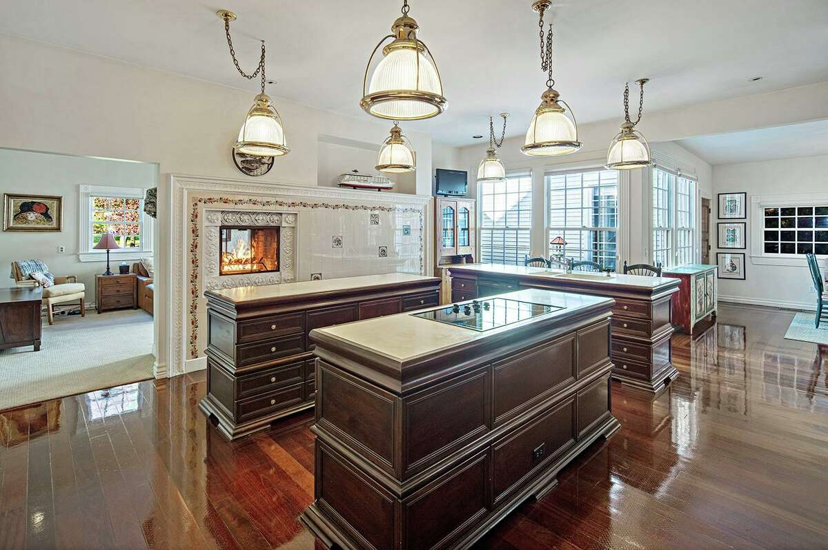 In the sizable gourmet eat-in kitchen there are three islands, a double-sided fireplace, and high end appliances.