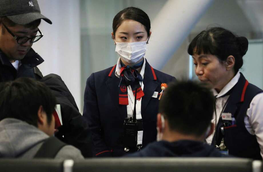 A Japan Airlines worker wears a face mask while Thursday in Los Angeles, California, amid fears of coronavirus. Photo: Mario Tama / Getty Images / 2020 Getty Images