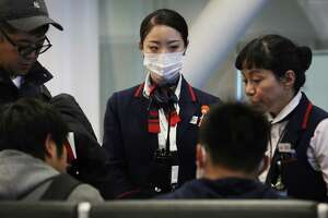 A Japan Airlines worker wears a face mask while Thursday in Los Angeles, California, amid fears of coronavirus.