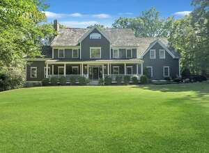 The charcoal gray custom-built colonial house at 19 Tall Pines Drive in Weston has 11 rooms, eight bathrooms, and 7,016 square feet of living space.
