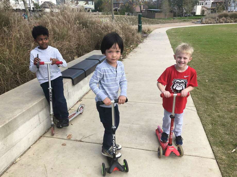Young pals (from left) Kiran, Jude and Jack take a break on their scooters at Evelyn's Park in Bellaire on January 6. The park has several wellness programs but also has lots of green space to relax and have fun. Photo: Tracy Maness / Staff Photo