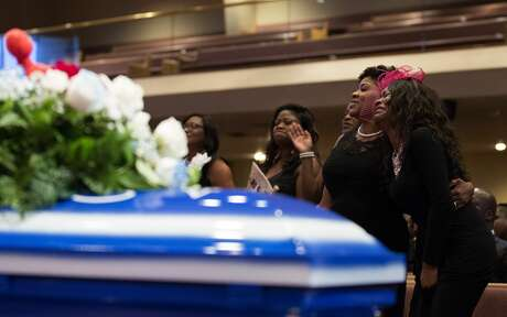 Roxane Freeman, right, grieves the death of her husband, Haywood, and children, Heywood Jr. and Halynn, during the funeral service at the Greater Grace Outreach Church Saturday, July 29, 2017, in Houston.