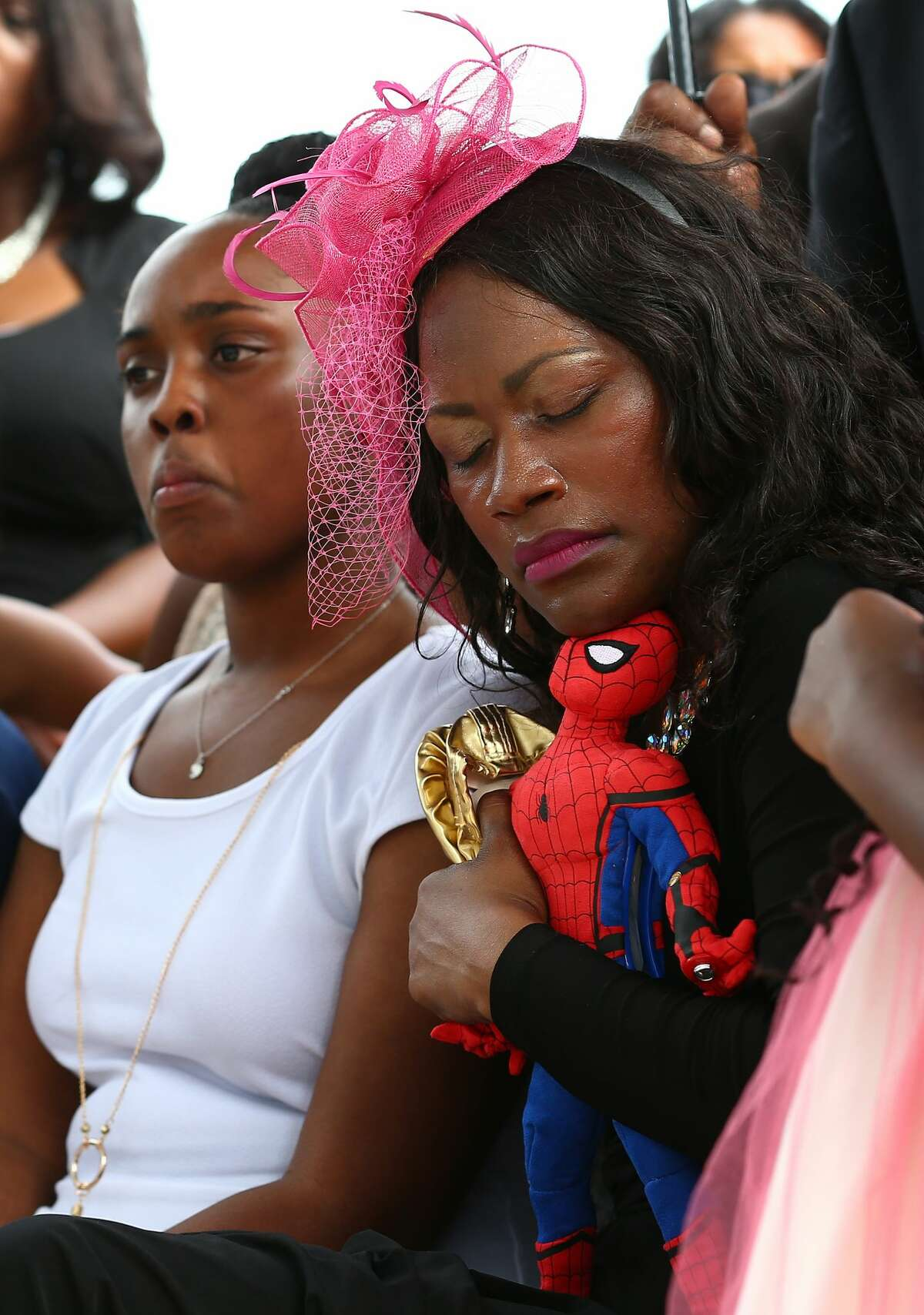 Roxane Freeman, center, holds tight her daughter's ballerina shoes, and her son's Sider-Man toy during the their burial at Paradise South Cemetery Saturday, July 29, 2017, in Houston.