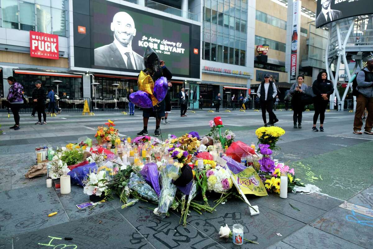 Flowers and candles are placed at a memorial for Kobe Bryant near Staples Center Monday, Jan. 27, 2020, in Los Angeles. Bryant, the 18-time NBA All-Star who won five championships and became one of the greatest basketball players of his generation during a 20-year career with the Los Angeles Lakers, died in a helicopter crash Sunday.