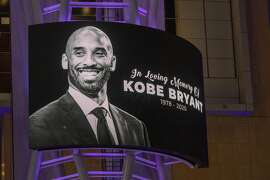 LOS ANGELES, CA - JANUARY 26: Memorial signage hangs near people mourning for former NBA star Kobe Bryant, who was killed in a helicopter crash in Calabasas, California, near Staples Center on January 26, 2020 in Los Angeles, California. Nine people have been confirmed dead in the crash, among them Bryant and his 13-year-old daughter Gianna. (Photo by David McNew/Getty Images)