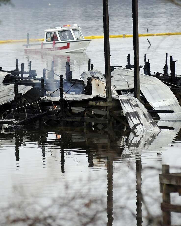 People on a boat patrol near the charred remains of a dock following a fatal fire at a Tennessee River marina in Scottsboro, Ala., Monday, Jan. 27, 2020. Authorities said the explosive fire was reported overnight while people were sleeping on boats tied up at the structure. (AP Photo/Jay Reeves) Photo: Jay Reeves, Associated Press