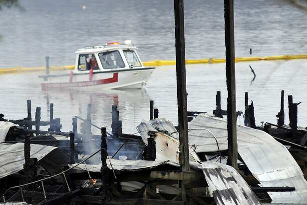 People on a boat patrol near the charred remains of a dock following a fatal fire at a Tennessee River marina in Scottsboro, Ala., Monday, Jan. 27, 2020. Authorities said the explosive fire was reported overnight while people were sleeping on boats tied up at the structure. (AP Photo/Jay Reeves)