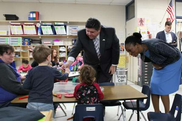 Gov. J.B. Pritzker, center, and Dr. Ngozi Ezike of the Illinois Department of Public Health, talk with children in the pre-Kindergarten program at Carlinville Intermediate School on Friday.
