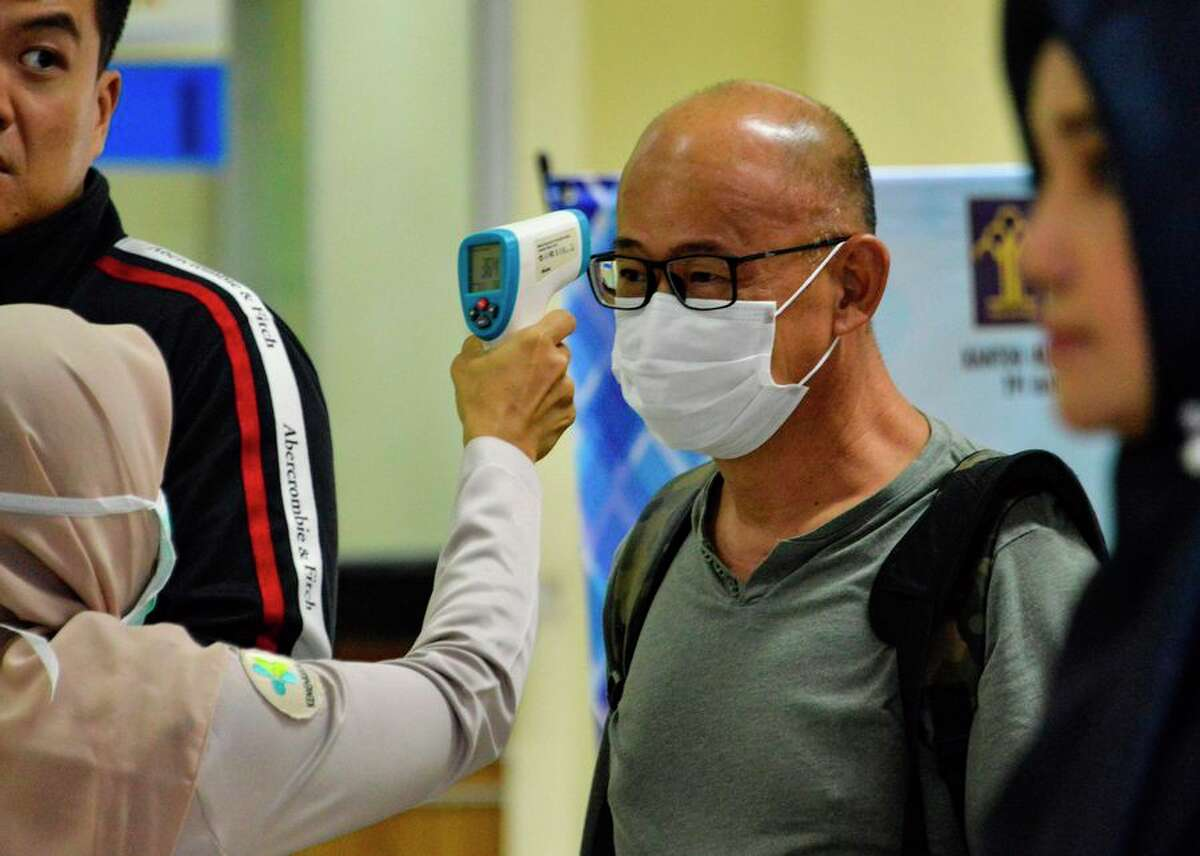 An Indonesian health official checks the temperature of a passenger upon his arrival at the Sultan Iskandar Muda International Airport in Blang Bintang on Jan. 27. By that date, an effective quarantine was in place in China, with all flights in and out of Wuhan grounded and a ban on Chinese tour groups domestically and abroad.