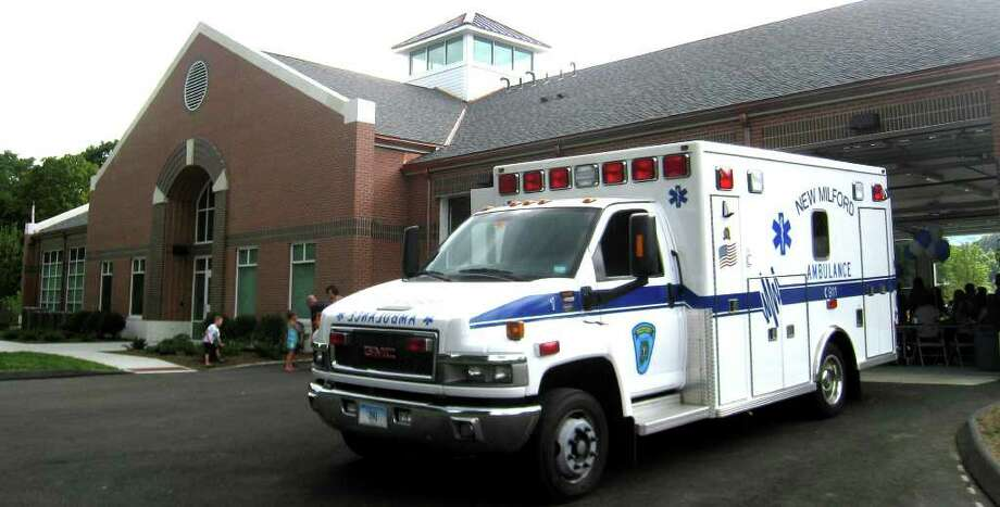 SPECTRUM/One of the ambulances sits ready to go on its next call, even as the festivities of the official unveiling of the new Scovill Street home for New Milford Community Ambulance lingers on late Friday afternoon in New Milford. Aug. 13, 2010 Photo: Norm Cummings / The News-Times