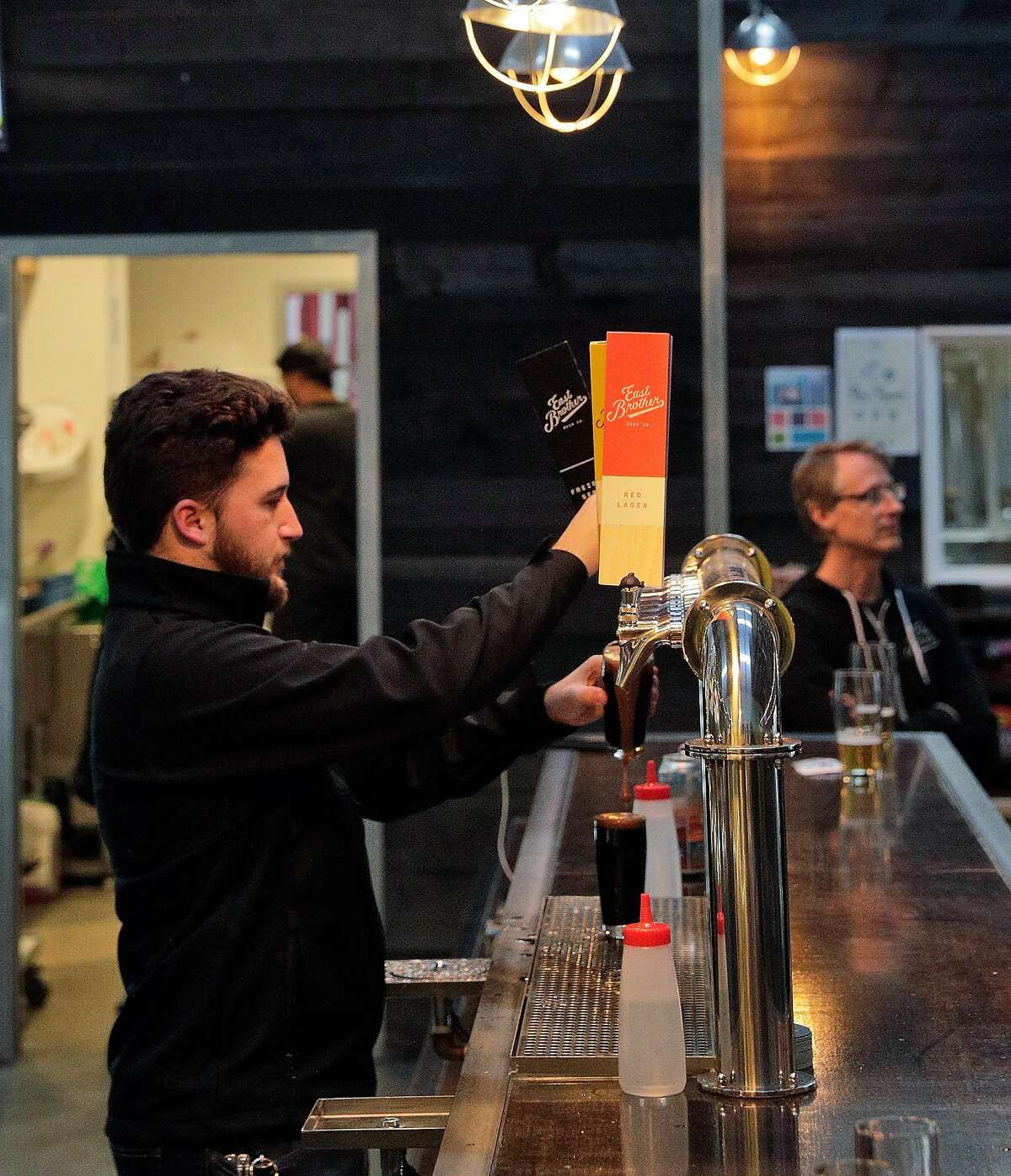 Bartender Gabriel Martin pours a beer behind the bar at East Brother Beer Company which is specializing in craft Lager beer in Richmond, Calif., on Thursday, January 16, 2020. There has been a rise of craft lager beers in the Bay Area, and unlike other local breweries that specialize in hoppy IPAs and sour beers, East Brother Beer Co. in Richmond focuses on classic, balanced lagers.