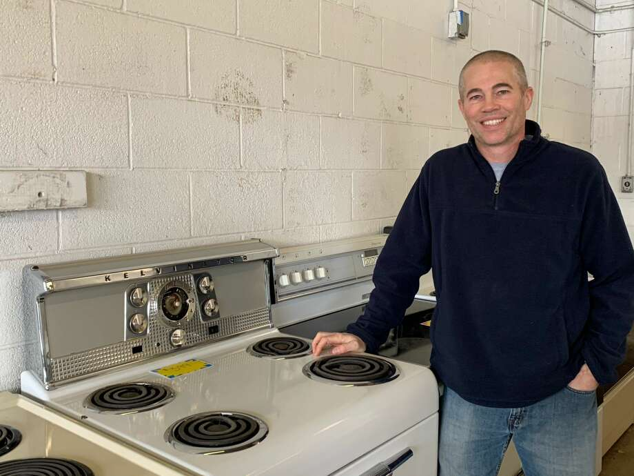 Darin Dana, Bullock Creek's new freshman boys' basketball coach, poses alongside a 1950s-era oven which has been restored by employees of Pivot Point Appliance in Midland. Photo: Fred Kelly/fred.kelly@mdn.net