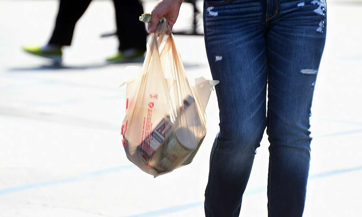 A woman carries her groceries in a plastic bag while leaving a supermarket in Monterey Park, California on September 30, 2014, where the state's Governor has signed the country's first statewide ban on single-use plastic bags from convenience and grocery stores. The ban, scheduled to take effect in July 2015, has led to a national coalition of plastic bag manufacturers immediately saying it will seek a voter referendum to repeal the law. AFP PHOTO / Frederic J. BROWN (Photo credit should read FREDERIC J. BROWN/AFP via Getty Images)