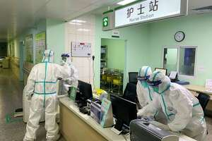 Medical staff members wear protective suits at the Zhongnan hospital in Wuhan in China's central Hubei province on Jan. 22, 2020. China banned trains and planes from leaving Wuhan at the center of a virus outbreak, seeking to seal off its 11 million people to contain the contagious disease that has claimed 17 lives, infected hundreds and spread to other countries.