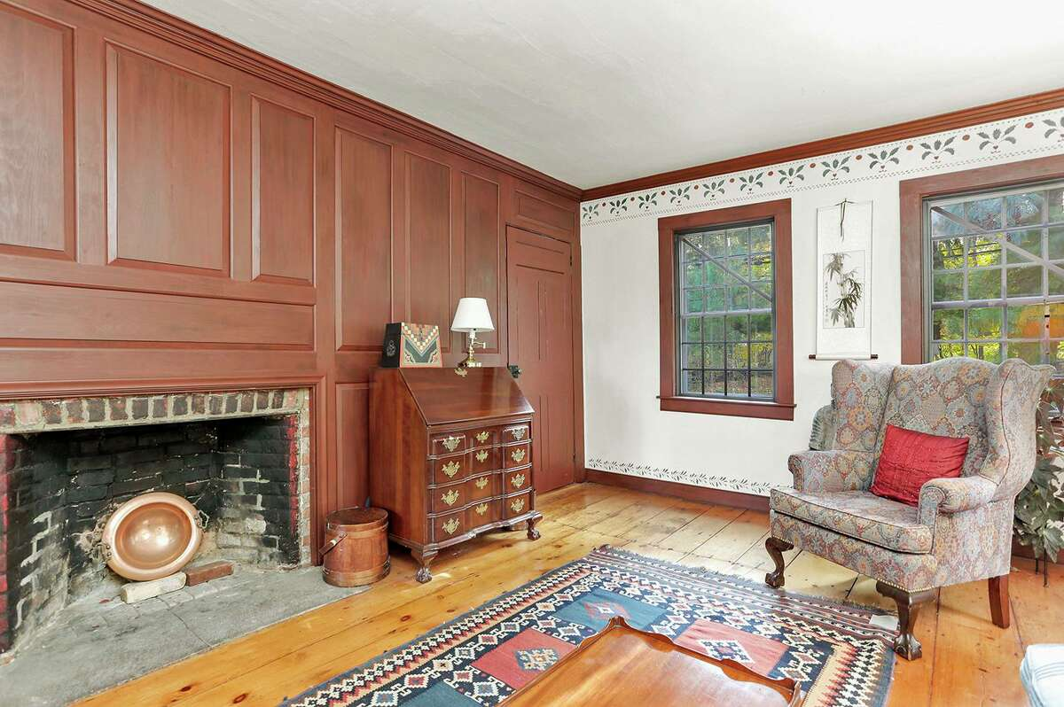 The living room features wide-planked wood flooring, and a wood paneled wall with a fireplace.