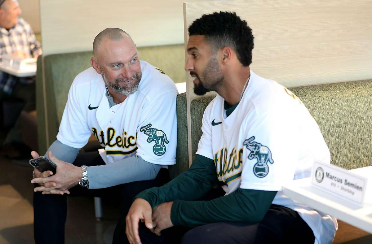 Mark Kotsay, quality control coach, left, and Marcus Semian, shortstop, converse during the Oakland A's pre-Fan Fest media availability at the A's offices at Jack London Square in Oakland, Calif., on Friday, January 24, 2020.